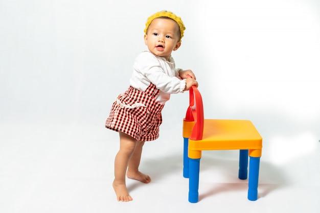 Foto do retrato do bebê pequeno, 9-10 meses, menina asiática que veste a camisa branca com a faixa colorida geral e amarela do cabelo, estando na cadeira plástica colorida, no fundo branco.
