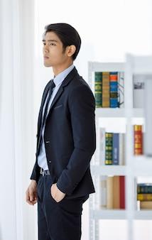 Foto do retrato do contador da empresa jovem asiática em terno preto formal e gravata em pé e olhar para fora, pensando ninhada, encontrando a ideia entre a estante na biblioteca.