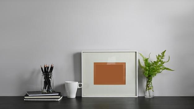 Foto do suporte do lápis, da pilha de livros, da moldura para retrato, do copo de café e da planta em pasta que montam na mesa de trabalho confortável com conceito em ordem do espaço de trabalho da sala de visitas.