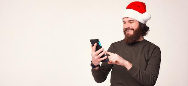 Foto do tamanho do banner de um homem barbudo com um chapéu de natal que está usando um tablet.