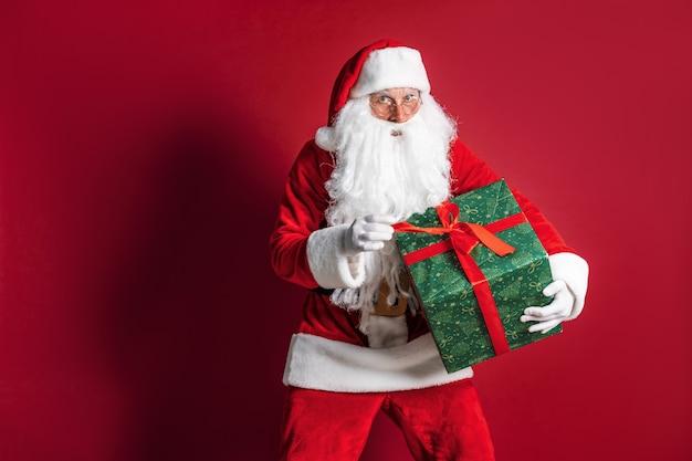 Foto do tipo papai noel dando presente de natal e olhando para a câmera