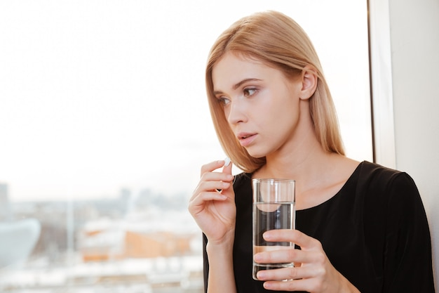 Foto do trabalhador jovem triste em pé no escritório, segurando um copo de água e pílula.