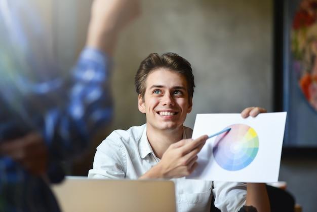 Foto do trabalho em equipe de designers de interiores com plantas de construção de casas na mesa de escritório, arquitetos trabalhando com uma paleta de várias cores para escolher a melhor cor para o design.