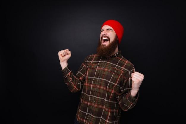 Foto do vencedor, um homem barbudo com chapéu vermelho, gritando com os olhos fechados e comemorando sobre uma parede escura
