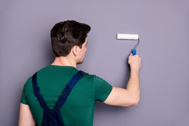Foto do verso traseiro de um trabalhador em foco, pintando o espaço usando uma escova de rolo branca, quer renovar seu apartamento usar uniforme verde de camiseta isolado sobre parede de cor cinza