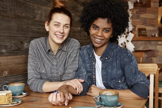 Foto doce da bela ruiva caucasiana feliz de mãos dadas com sua estilosa namorada afro-americana