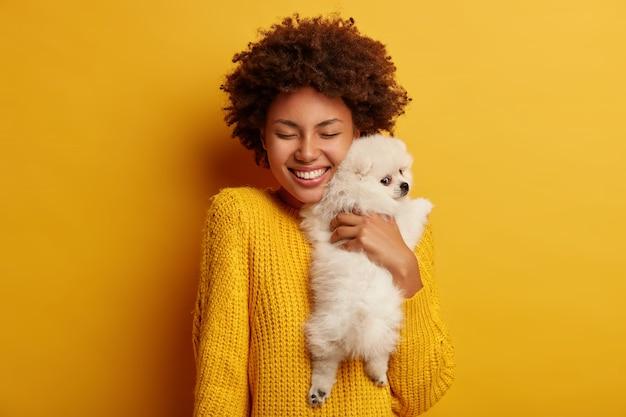 Foto doce de mulher afro alegre abraçando com grande amor seu cachorro spitz