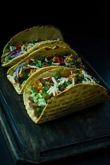 Foto dos tacos mexicanos com carne, queijo, milho, cebolas e ervas da carne de porco em uma placa de madeira. molho de ketchup e pimenta.