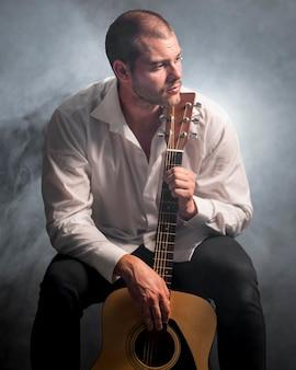 Foto editada de homem e violão na fumaça