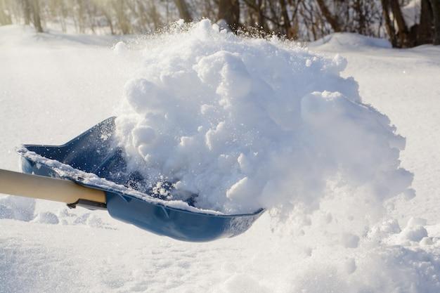Foto em ação. jogando neve com pá durante a limpeza do quintal