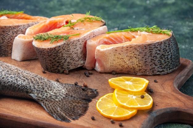 Foto em alta resolução de peixes crus frescos rodelas de limão, verdes, pimenta na tábua de madeira na mesa de cores escuras