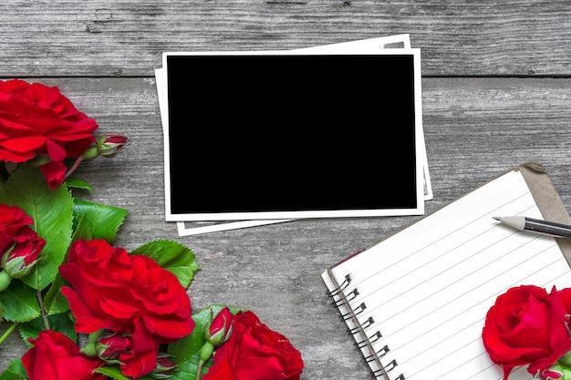 Foto em branco com buquê de flores rosas vermelhas e caderno pautado