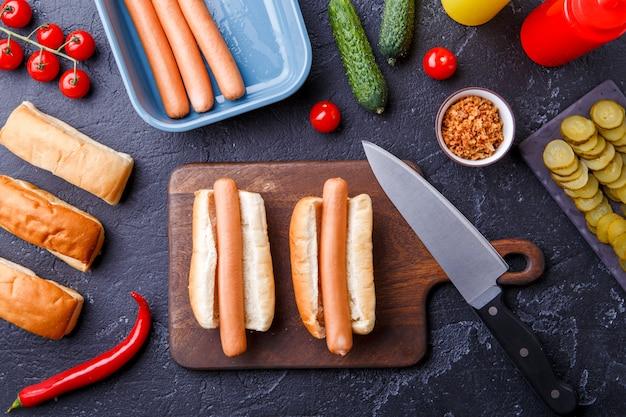Foto em cima de dois cachorros-quentes na tábua na mesa com salsichas