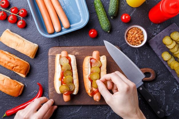 Foto em cima de dois cachorros-quentes no tabuleiro na mesa com mãos humanas