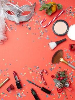 Foto em cima de pincéis, máscara de pena, tangerina, cana-de-açúcar na mesa vermelha vazia