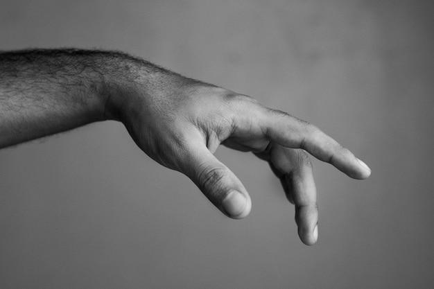 Foto em escala de cinza da mão de um homem mostrando um gesto