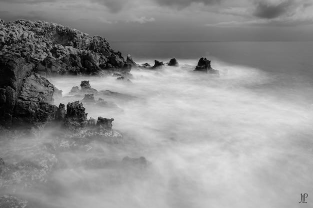 Foto em escala de cinza das rochas no corpo do mar espumoso