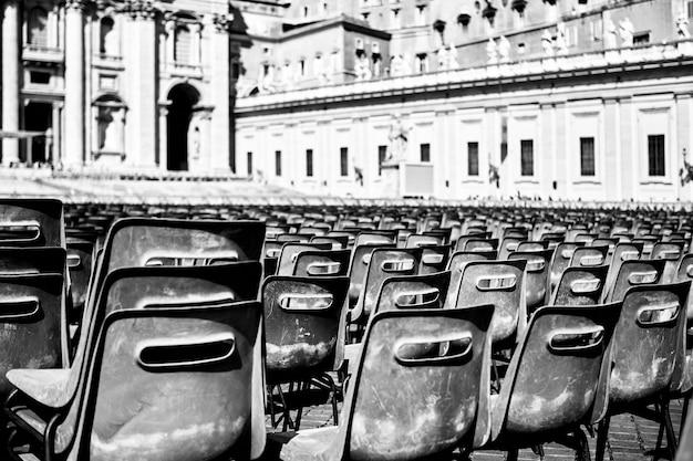 Foto em escala de cinza de cadeiras de plástico preto em uma praça em roma