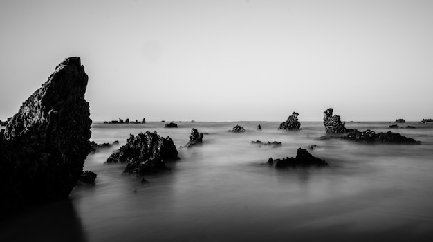 Foto em escala de cinza de formações rochosas no mar