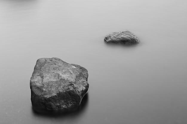 Foto em escala de cinza de formações rochosas no oceano congelado coberto por névoa