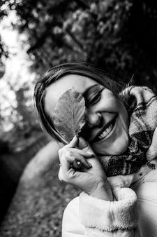 Foto em escala de cinza de mulher segurando uma folha