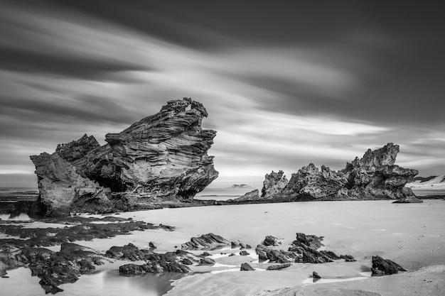 Foto em escala de cinza de rochas na praia com céu nublado