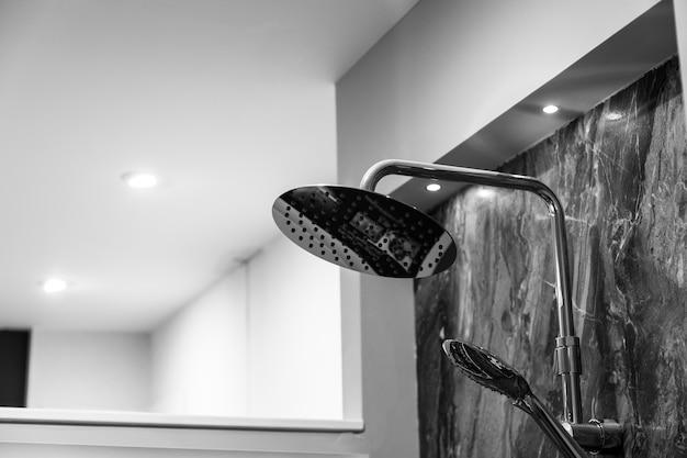Foto em escala de cinza de um chuveiro preso a uma parede de mármore em um banheiro