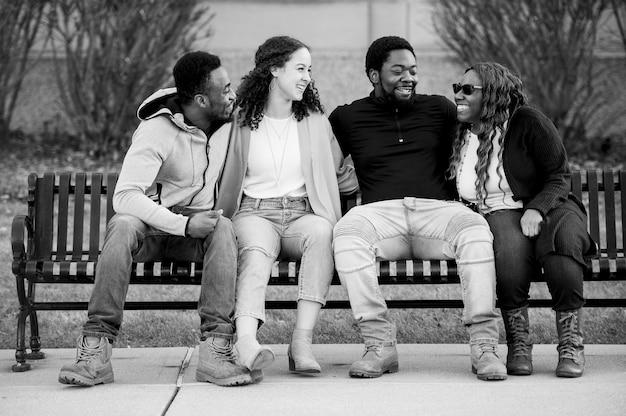 Foto em escala de cinza de um grupo de amigos sentados alegremente em um banco