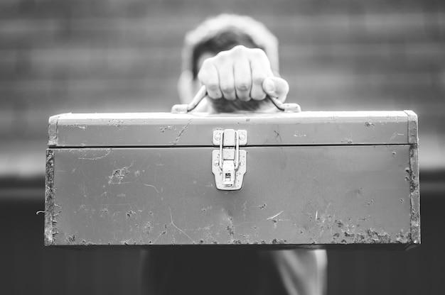 Foto em escala de cinza de um homem segurando uma caixa de ferramentas na frente do rosto