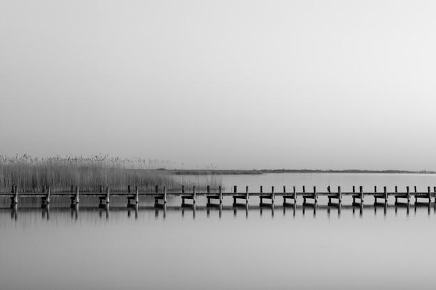 Foto em escala de cinza de um píer de madeira perto do mar durante o dia