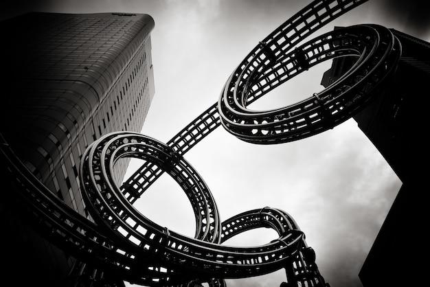 Foto em escala de cinza de um prédio alto ao lado de um objeto projetado para se parecer com uma fita de filme