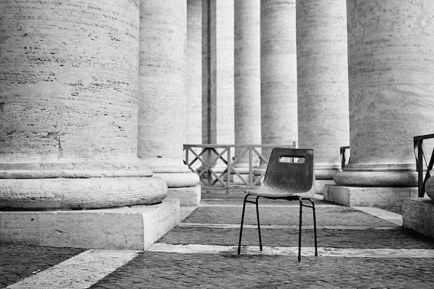Foto em escala de cinza de uma cadeira de plástico abandonada em um prédio com colunas em roma