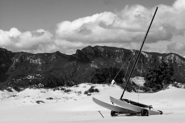 Foto em escala de cinza de uma canoa a vela sobre rodas em montanhas nevadas