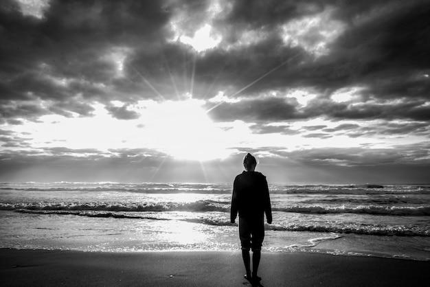 Foto em escala de cinza de uma mulher em pé na praia com a luz do sol no céu nublado