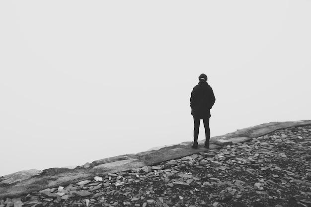 Foto em escala de cinza de uma pessoa parada na beira de um penhasco olhando para o vazio branco