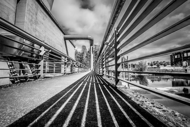 Foto em escala de cinza de uma ponte sob um céu nublado