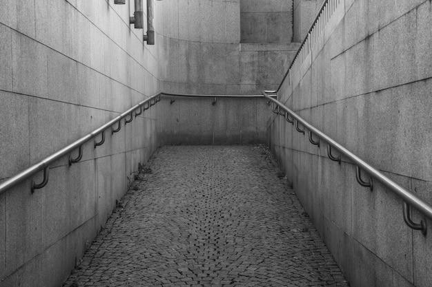 Foto em escala de cinza de uma rampa para cadeiras de rodas perto de um prédio, capturada durante o dia