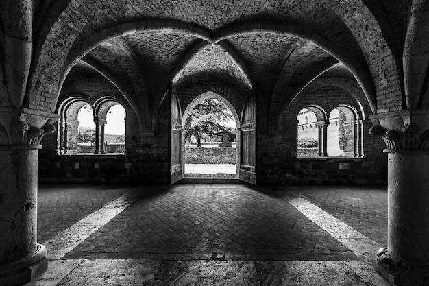 Foto em escala de cinza dentro da abadia de são galgano, na toscana, itália, com paredes em arco