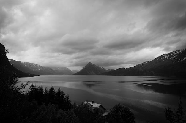 Foto em escala de cinza do lago cercado por montanhas e árvores
