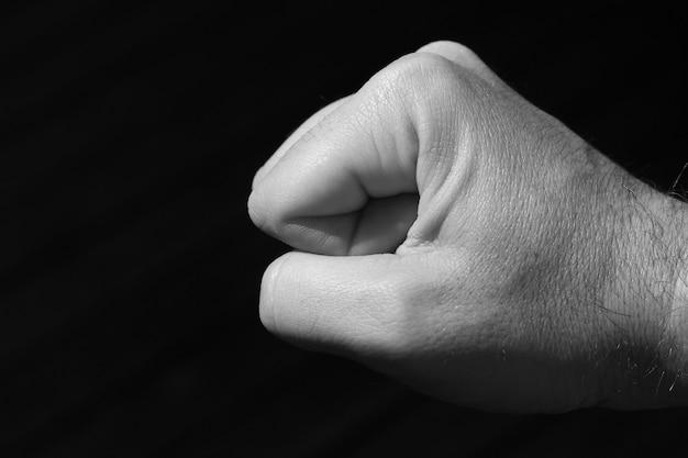 Foto em escala de cinza do punho de uma pessoa em um fundo preto