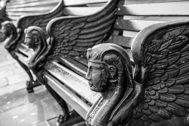 Foto em escala de cinza dos bancos de pedra lindamente decorados, capturada em londres, inglaterra
