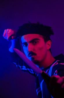 Foto em foco raso de homem segurando uma faca