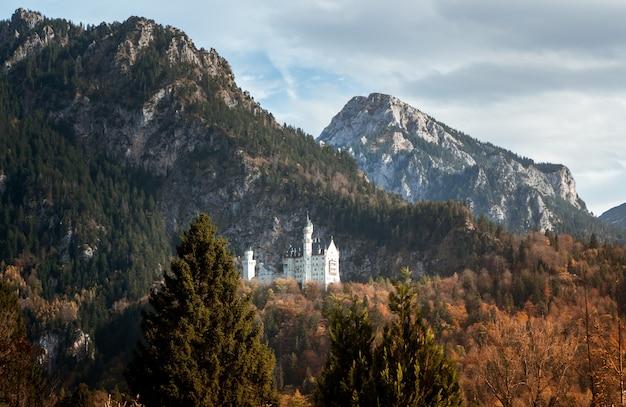 Foto em grande angular do castelo de neuschwanstein, na alemanha, atrás de uma montanha cercada pela floresta