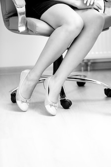 Foto em preto e branco aproximada de pés de mulheres empresárias em sapatilhas sob a mesa do escritório
