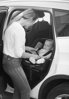 Foto em preto e branco da mãe acomodando o filho na cadeirinha do carro