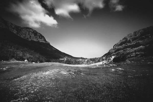 Foto em preto e branco de belos prados entre duas altas montanhas