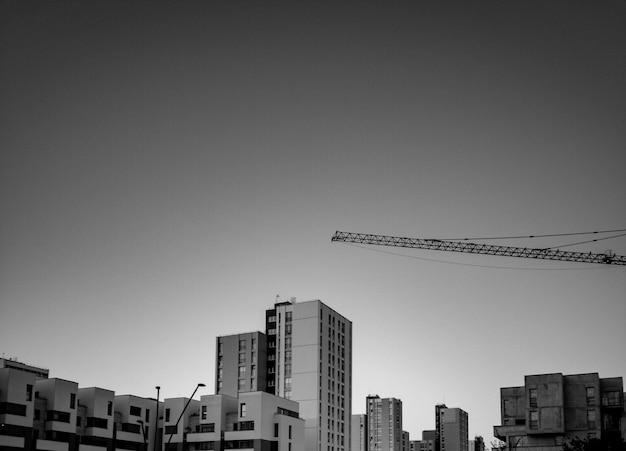 Foto em preto e branco de edifícios e guindaste