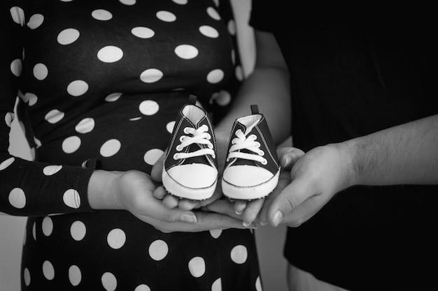 Foto em preto e branco de grande plano de pais grávidas segurando botas de bebê nas mãos