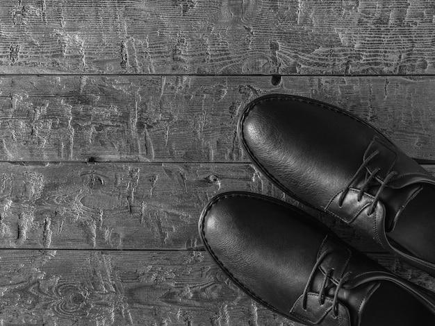 Foto em preto e branco de sapatos masculinos clássicos em um chão escuro