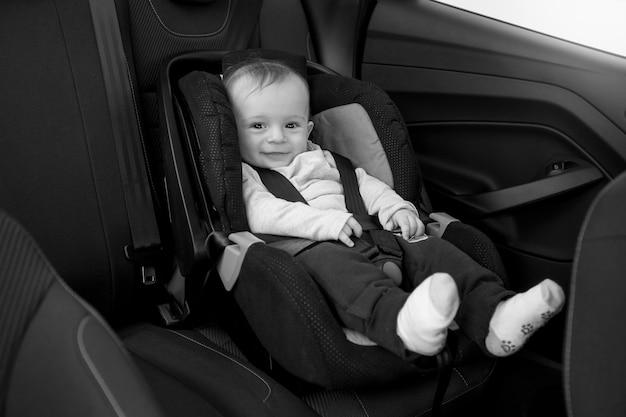 Foto em preto e branco de um bebê sorridente sentado na cadeira do carro